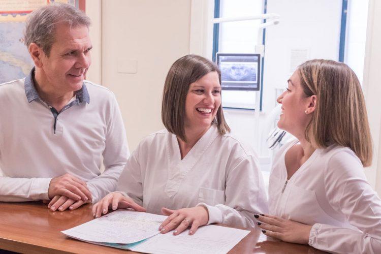 il dentista e le sue assistenti si consultano sulla cartella di un cliente